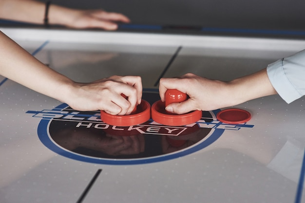 Hands of young people holding striker on air hockey table in game room Premium Photo
