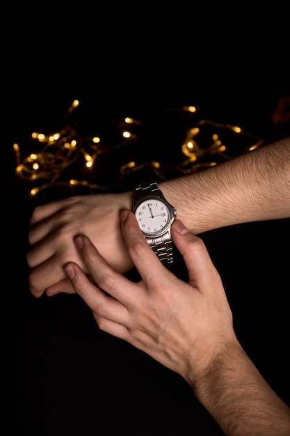 Hands of a young person looking at a clock about to mark the first second of the new year 2019 Premium Photo