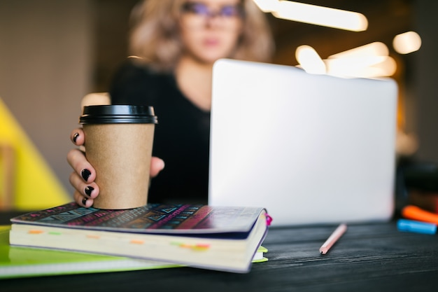 Hands of young pretty woman sitting at table in black shirt working on laptop in co-working office Free Photo