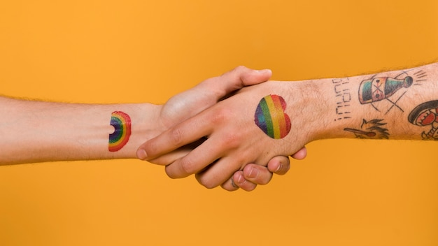 Handshake of couple of man hands with gay pride multicolored pattern Free Photo