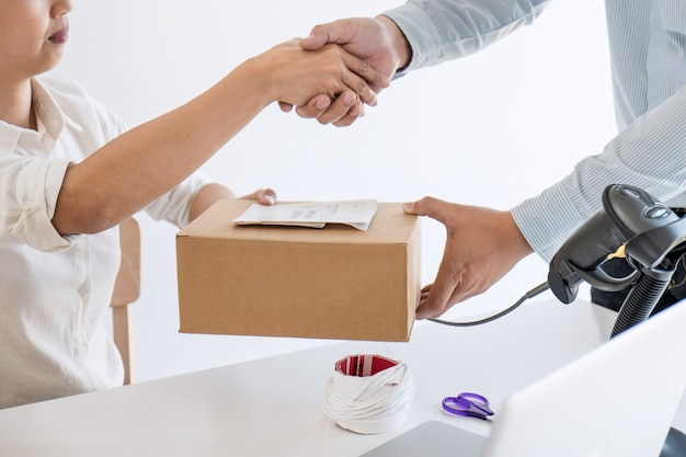 Handshake of entrepreneur sme to receive order client and working with packaging Premium Photo