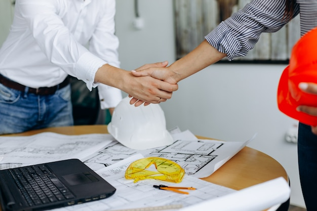 Premium Photo   Handshake of two businesspeople after architect working and  planning blueprint