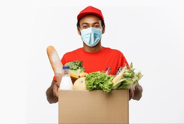 Коробка нося пакета красивого афро-американского работника доставляющего покупки на дом еды и питья бакалеи от магазина. Premium Фотографии