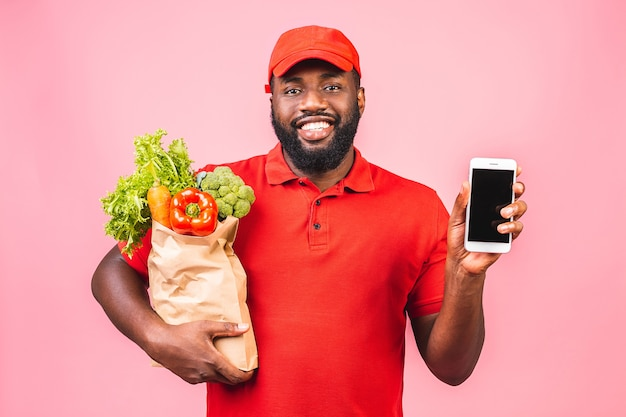 Красивый афро-американский доставщик, несущий пакетную коробку продуктовой еды из магазина Premium Фотографии