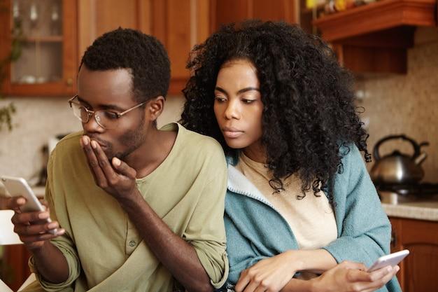 Красивый афро-американский мужчина в очках читает смс на мобильном телефоне Бесплатные Фотографии