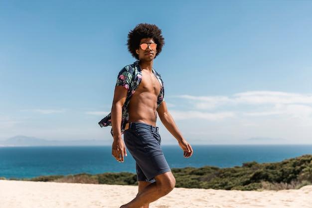 Handsome african american man walking on beach Free Photo
