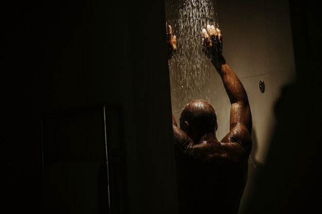 Handsome african american man with naked torso takes shower Free Photo