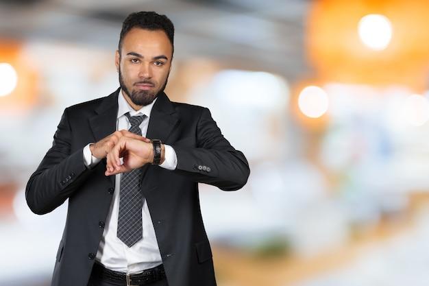 Красивый афро-американский молодой человек, глядя на часы. копировать пространство Premium Фотографии