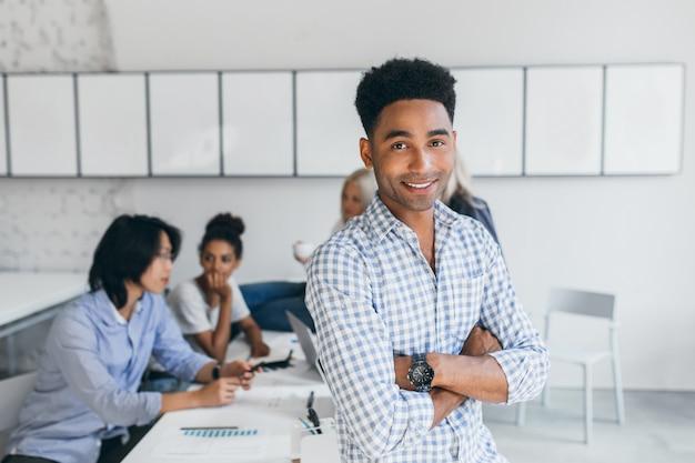 Красивый африканский мужчина сидит за столом в офисе, пока его подчиненные работают над новой стратегией продаж. внутренний портрет деловых людей международной компании, позирующих во время рабочего процесса. Бесплатные Фотографии