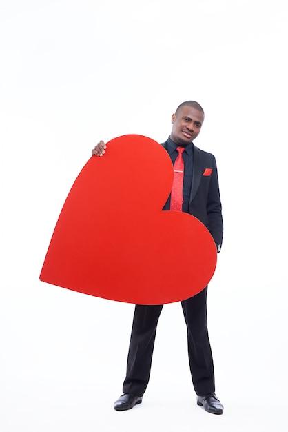 黒のスイートと大きな赤いハートを保持している赤いネクタイを着ているハンサムなアフリカ人 無料写真