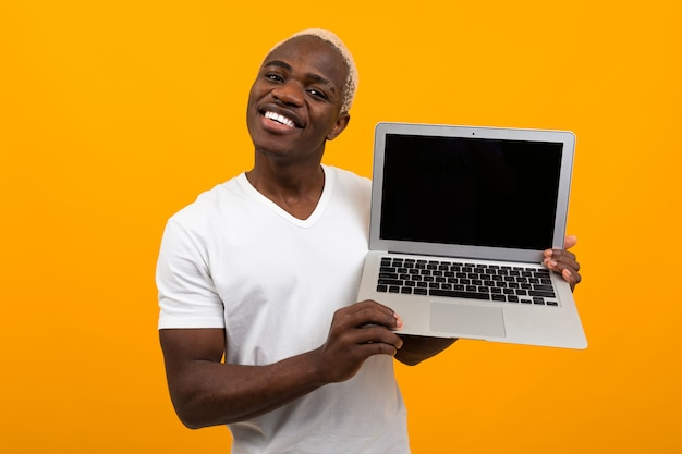 Handsome african man with pretty smile holds laptop wireless computer with mock up on yellow background Premium Photo