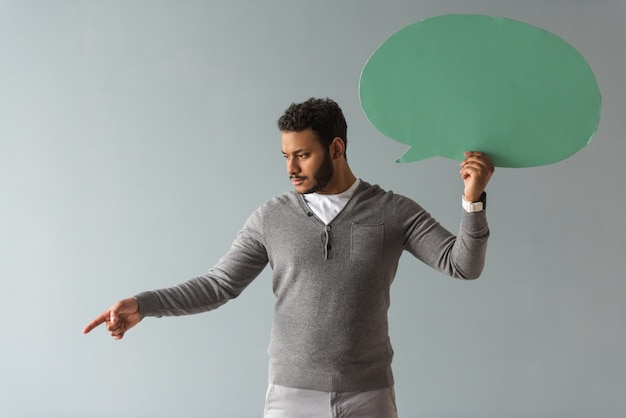 Handsome afro american guy is holding a speech bubble. Premium Photo