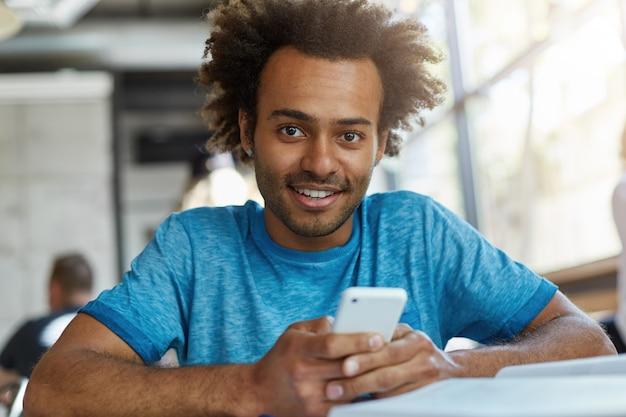 Bel ragazzo afroamericano con la testa di capelli ricci seduto in una caffetteria accogliente che tiene il telefono intelligente che scarica musica utilizzando la connessione internet gratuita che sembra felice ed eccitato sorridente Foto Gratuite