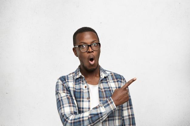Красивый удивленный и удивленный молодой темнокожий студент или клиент в очках и клетчатой рубашке, указывая указательным пальцем Бесплатные Фотографии