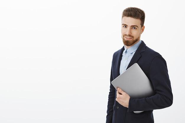 ハンサムでスタイリッシュなビジネスマンは、ビジネスの仕組みを知っています。ラップトップコンピューターを手に持って、灰色の壁に自信を持って見つめるスーツを着た、成功し、断固とした見栄えの良い男 無料写真