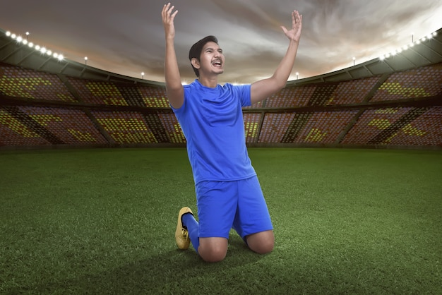 Handsome asian football player happy for winning the match Premium Photo