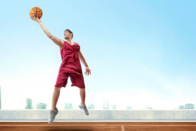 Handsome asian man basketball player jumping high and rebound the ball to score in outdoor basketball court Premium Photo