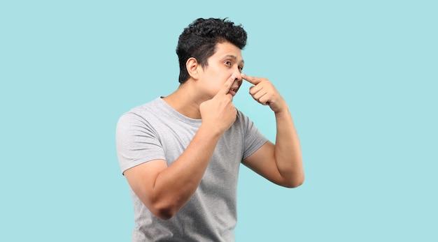 잘 생긴 아시아 남자 그의 얼굴을 만지고, 여드름을 압박 프리미엄 사진