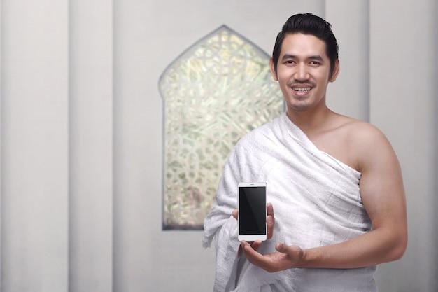 Handsome asian muslim man wearing ihram clothes holding mobile phone Premium Photo
