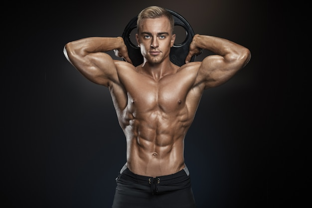 Handsome athletic guy posing with barbell plate Premium Photo