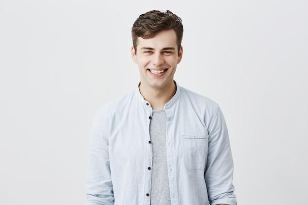 ハンサムな魅力的な若い男は、暗い髪のtシャツの上に水色のシャツに身を包み、魅力的な青い目looknig、広く笑って、白い歯を見せて、幸せで満足しています。 無料写真