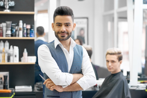 Handsome barber posing standing in front of young client sitting near mirror. Premium Photo