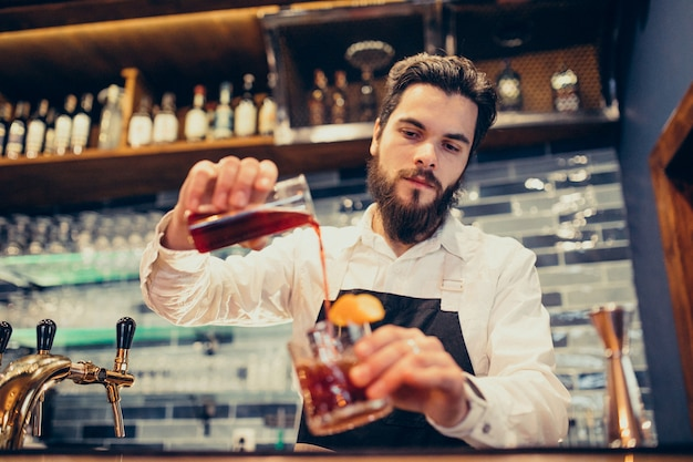 Handsome bartender making drinking and cocktails at a counter Free Photo