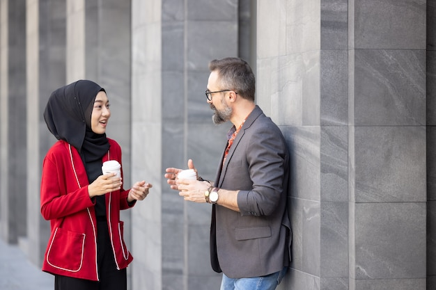 Handsome beard middle aged businessman drinking coffee at outdoor coffee cafe with young beautiful muslim woman Premium Photo