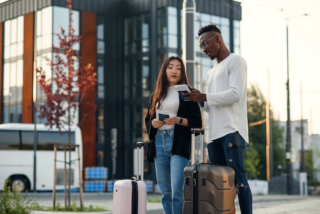 Красивый бородатый афро-американский парень и азиатская красивая девушка собираются в командировку с чемоданами, ожидающими на остановке. Premium Фотографии
