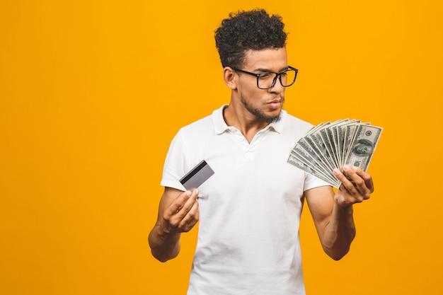 お金とクレジットカードのスタックを保持しているハンサムなひげを生やしたアフリカ系アメリカ人 Premium写真