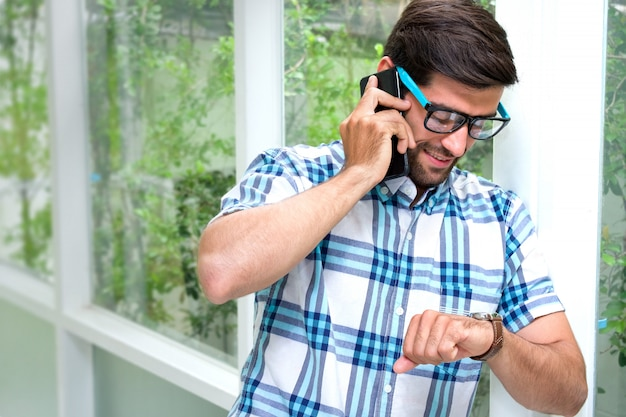 Handsome bearded guy wearing glasses is looking the watch while talking on cellphone when approaching work time. Premium Photo