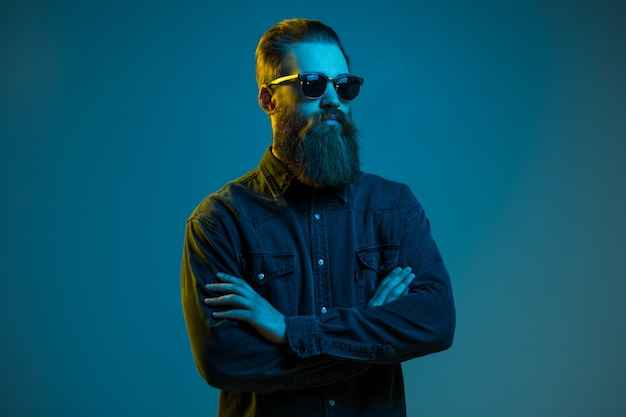 Handsome bearded hipster man wearing round sunglasses isolated over blue light space Premium Photo