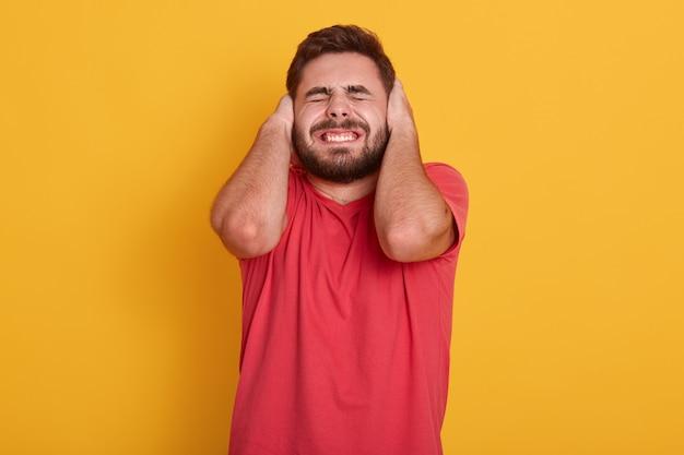 Красивый бородатый мужчина носить красную футболку, привлекательный мужчина позирует с закрытыми глазами и ушами, слышать громкий шум, парень стоял изолированные на желтом. концепция людей. Бесплатные Фотографии