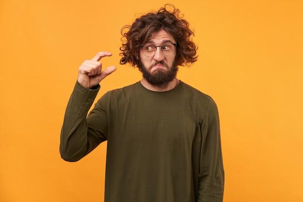 Bel maschio barbuto con capelli ricci scuri, mostra qualcosa di minuscolo con le mani Foto Gratuite