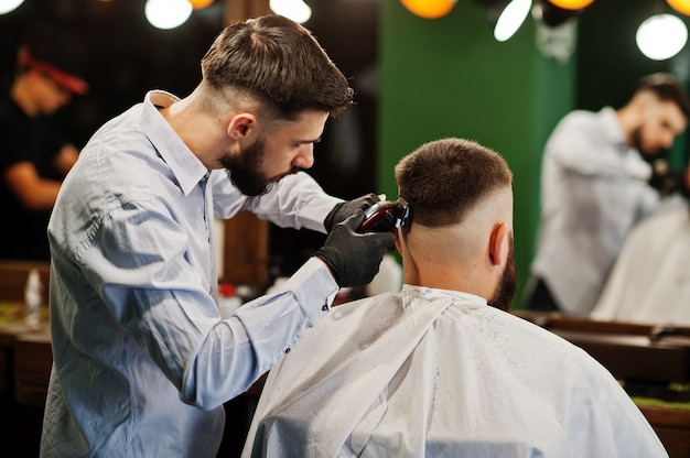 Premium Photo | Handsome bearded man at the barbershop, barber at work.