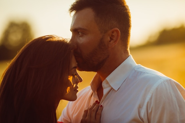Handsome bearded man kisses woman's head tender standing in a golden summer field Free Photo
