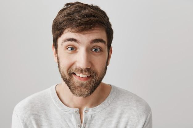 Красивый бородатый мужчина выглядит заинтригованным и улыбается Бесплатные Фотографии