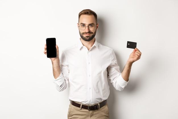 携帯電話とクレジットカードを示して、オンラインショッピング、立っているハンサムなひげを生やした男 無料写真