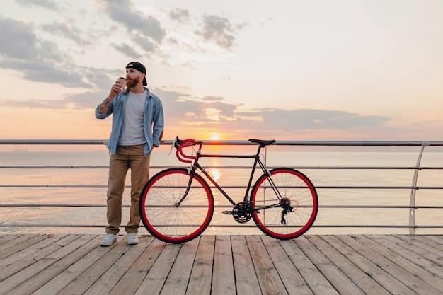 Uomo barbuto bello che viaggia con la bicicletta nell'alba di mattina in riva al mare a bere caffè, viaggiatore sano stile di vita attivo Foto Gratuite