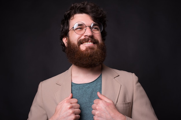 Красивый бородатый мужчина в очках улыбается, глядя вверх, держа куртку. Premium Фотографии