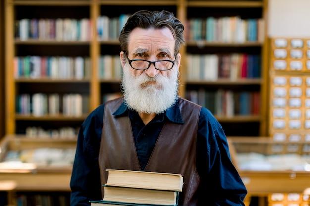 ハンサムなひげを生やした上級学術教授または図書館労働者、笑みを浮かべて、古い本を保持しながら、ヴィンテージ図書館の本棚の背景の上に立っています。知識の概念 Premium写真