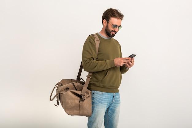 Красивый бородатый стильный мужчина в толстовке с дорожной сумкой, в джинсах и солнцезащитных очках изолировал телефон в руке Бесплатные Фотографии