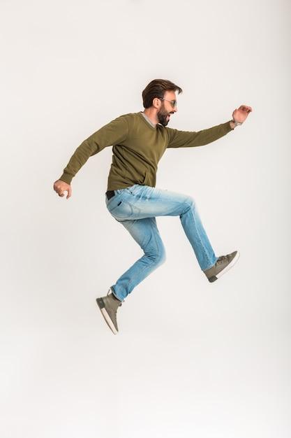 Uomo alla moda barbuto bello che salta in esecuzione isolato vestito in felpa, jeans e occhiali da sole Foto Gratuite