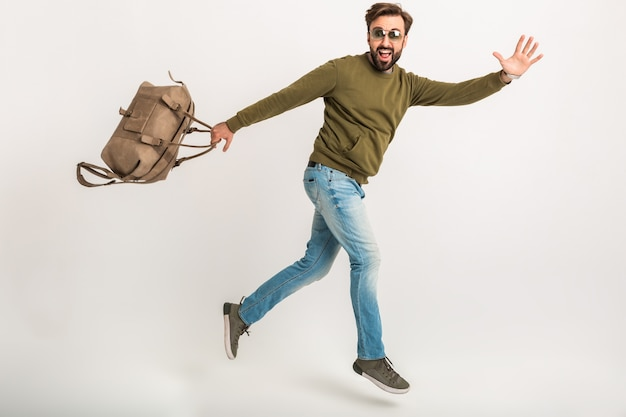 Bell'uomo barbuto elegante che salta in esecuzione isolato vestito in felpa con borsa da viaggio, indossa jeans e occhiali da sole, viaggiatore pazzo in fretta Foto Gratuite