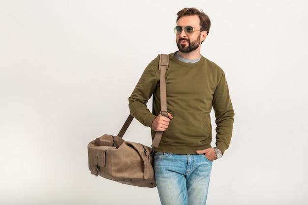 旅行バッグとスウェットシャツを着て、ジーンズとサングラスを身に着けている孤立したポーズをとってハンサムなひげを生やしたスタイリッシュな男 無料写真