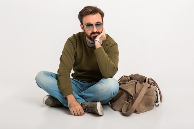 Uomo elegante barbuto bello che si siede sul pavimento isolato vestito in felpa con borsa da viaggio, jeans e occhiali da sole, attesa triste e stanca Foto Gratuite