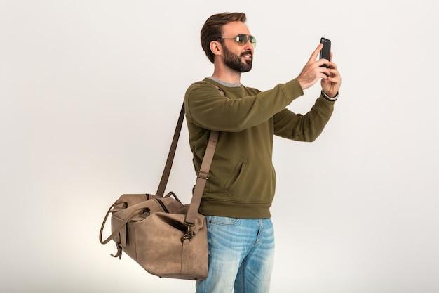 Uomo alla moda barbuto bello in felpa con borsa da viaggio, indossa jeans e occhiali da sole isolati prendendo selfie foto sul telefono Foto Gratuite