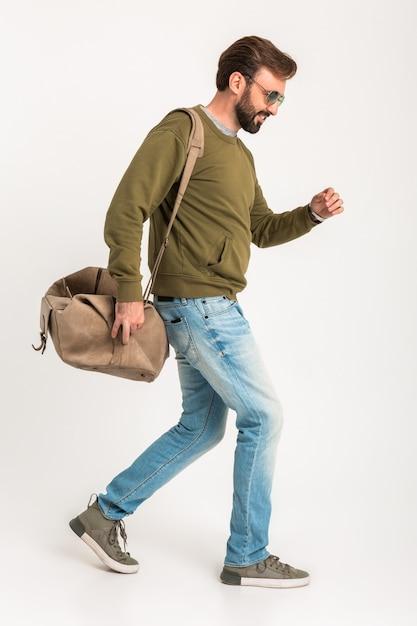 Uomo alla moda barbuto bello camminare isolato vestito in felpa con borsa da viaggio, indossa jeans e occhiali da sole Foto Gratuite