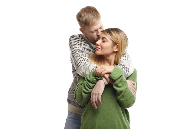 Handsome bearded young male hugging his cute girlfriend and kissing her on forehead, expressing his love and tenderness. beautiful couple cuddling after long separation, keeping eyes closed Free Photo