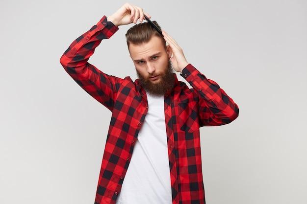 モダンな髪型をしているシャツのハンサムなひげを生やした若い男、白い背景の上に分離された櫛で彼の髪を手入れする 無料写真
